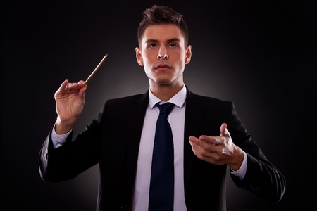 Portrait of a young conductor directing his orchestra. Leadership concept. Young businessman directing with a conductors stick. photo