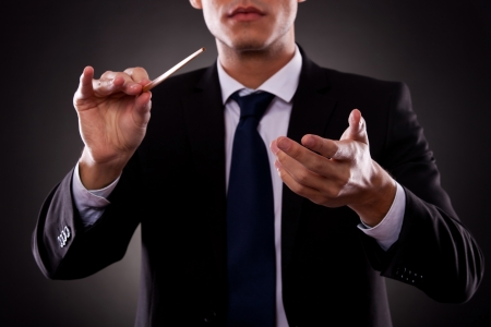 conduct: Cutout picture of a young orchestra conductor directing with his baton