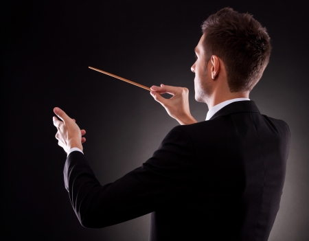 conductor: Back view of a young composer directing with his baton, on black background