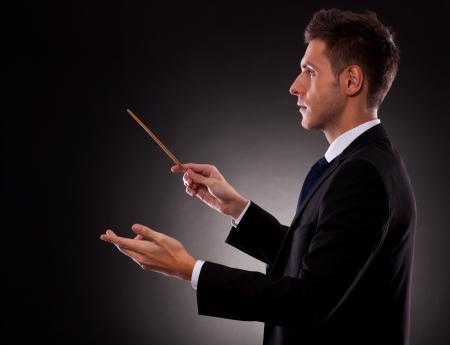 orquesta clasica: Vista lateral de un hombre de negocios joven director con una batuta Foto de archivo