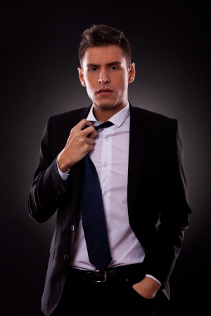 A Young businessman loosing his tie. on black background photo