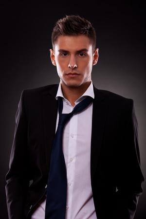 waistup: waist-up retrato de un joven hombre de negocios con la corbata floja, con las manos en los bolsillos