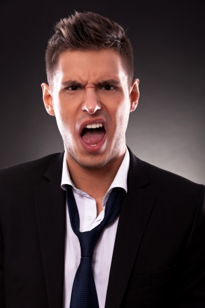 angry businessman: portrait of an angry young businessman shouting
