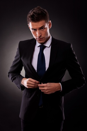 suit tie: businessman buttoning jacket, getting dressed, on dark background  Stock Photo