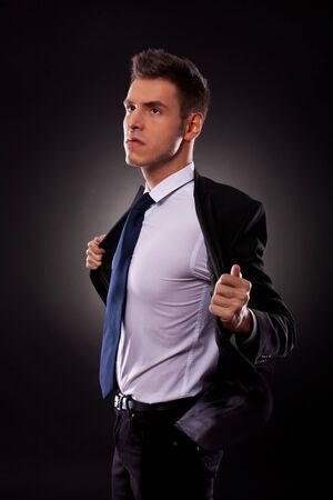 angry businessman: 45 degree angle view of a young businessman taking off his jacket angrily, looking away from camera Stock Photo
