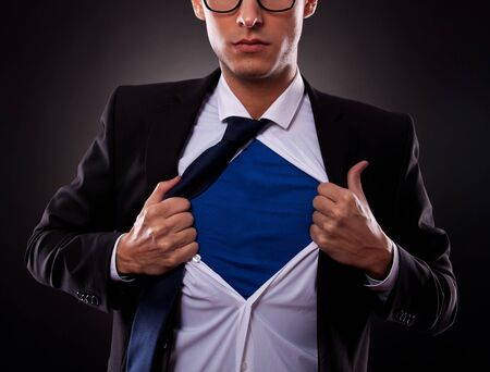 cropped off: Cropped view of young business man tearing off his shirt on black background Stock Photo