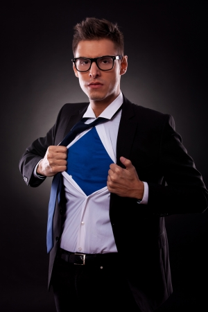 unsuccessful: Young business man ripping off his shirt on black background