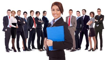 Líder sosteniendo un portapapeles con equipo de negocios detrás, aislado en blanco. businessteam acertado feliz con una mujer joven como líder, con un bloc de notas y mirando a la cámara