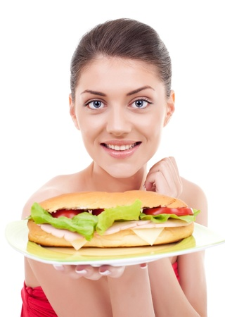 Awesome young woman presenting a delicious sandwich on a plate and smiling at the camera. Isolated on black background photo