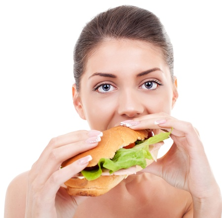 Close-up of a beautiful young woman taking a big bite of a sandwich while looking at the camera photo