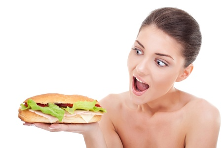 Young woman holding and looking at a sandwich and acting surprised and amased photo