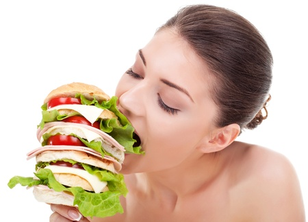 latin food: young woman biting a big sandwich, isolated on white background