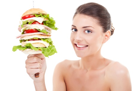 Young  woman holding a big sandwich on a spike and smiling at the camera, on white background. photo