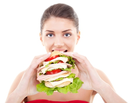 smiling young woman preparing to eat a huge sandwich on white background  photo