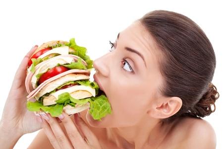 malos habitos: Mujer joven mordiendo un pan hecho en casa muy grande lleno de tomate y tocino en un fondo blanco