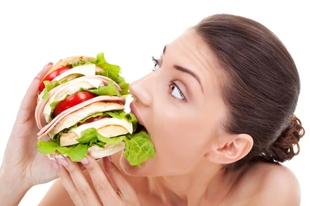 weight gain: Young woman biting into a very big homemade bread roll filled with tomato and bacon on a white background