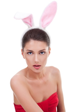 playboy: Portrait of an awesome young woman in red dress wearing rabbit ears and looking sensually into the camera.