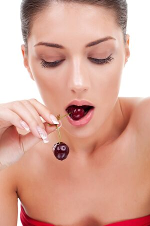 Healthy young woman eating red cherries and looking down isolated on white  photo