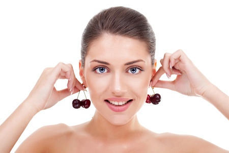 Beautiful young woman holding cherries insead of earrings photo