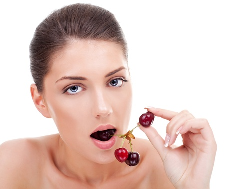 Closeup portrait of young beautiful woman eating cherry in her lips and hand  Stock Photo - 15154716