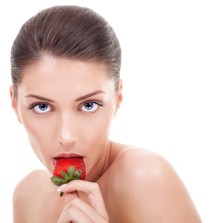 Closeup of sensuous young woman eating strawberry over white background  photo