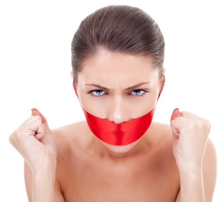 frustrated young woman with a red silk ribbon covering her mouth, on white background photo