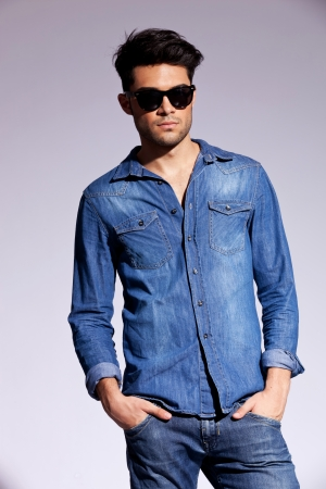 trendy: attractive man dressed casually in a jeans shirt,  wearing sunglasses Stock Photo
