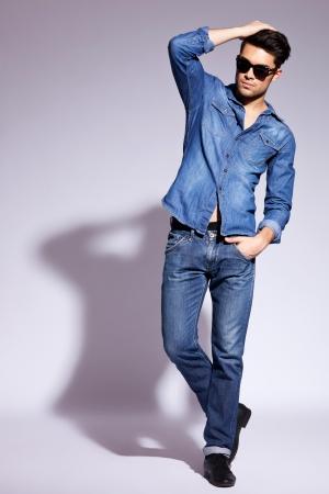 poses de modelos: sexy joven modelo masculino moviendo su mano por el pelo