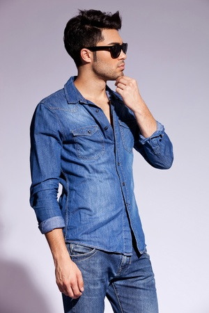 studio side view of a handsome young male model wearing jeans shirt and sunglasses  Stock Photo - 15154781