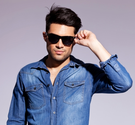 Fashion young man holding his fashionable sunglasses on gray background photo