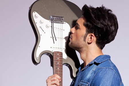 man side: young man guitarist in love with his electric guitar on gray background
