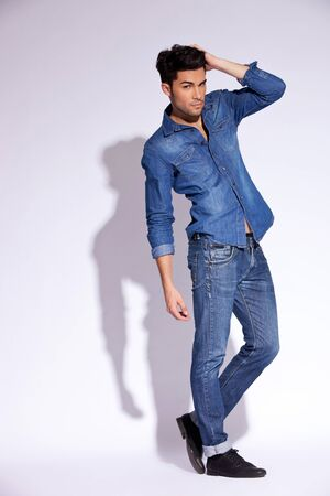 full body picture of a fashion young man with his hand on head photo