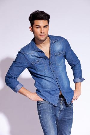 스튜디오에서 캐주얼 청바지 셔츠 포즈를 착용하는 젊은 남성 모델