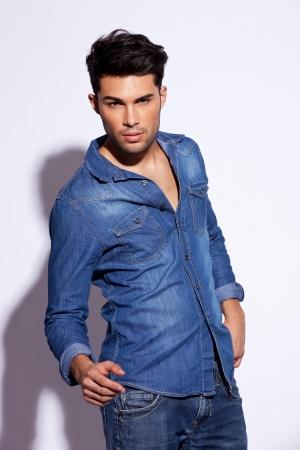 jonge mode man poseren voor de camera op een grijze achtergrond Stockfoto