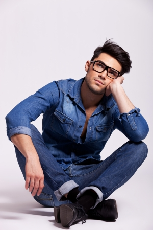 attractive young fashion man wearing glasses, sitting and thinking on a gray studio background photo