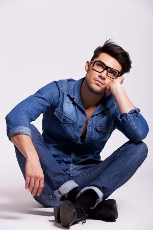 hombre sentado: hombre atractivo de moda joven con gafas, sentado y pensando en un fondo gris estudio