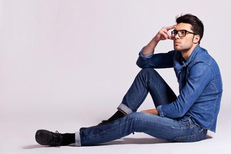 vista lateral de un hombre de moda casual sentado sobre fondo gris y mirando a la cámara Foto de archivo