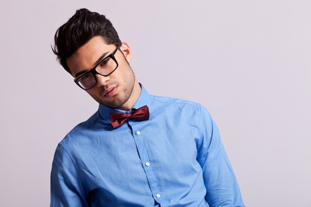 hair bow: fashion young man wearing glasses and bow tie leaning to his side on gray background