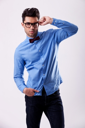 young fashion male model wearing bow tie and holding his glasses on gray background photo