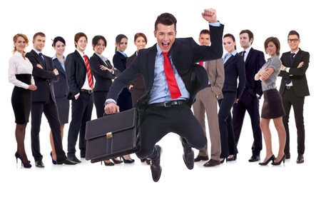 business man holding briefcase jumping with his business team formed of young businessmen and businesswomen standing over a white background photo