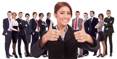 young business woman leader is very happy about the results , making the ok sign with her team behind, on white background photo