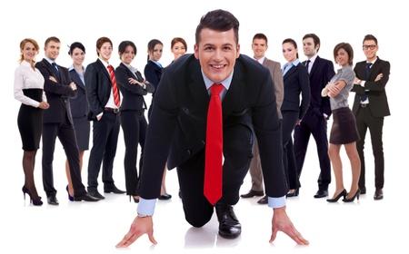 begining: azienda leader davanti alla sua squadra in piedi in una posizione di inizio della gara, isolato su bianco. Archivio Fotografico