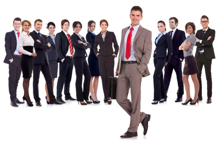 Business leader  with briefcase in his hand, isolated on white . young business man with suitcase looking at  the camera with a large business team behind him  photo
