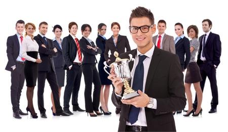 rewarded: equipo ganador de negocio con un ejecutivo joven sosteniendo un trofeo de oro. bueinssteam feliz y exitoso recompensados ??por su trabajo Foto de archivo