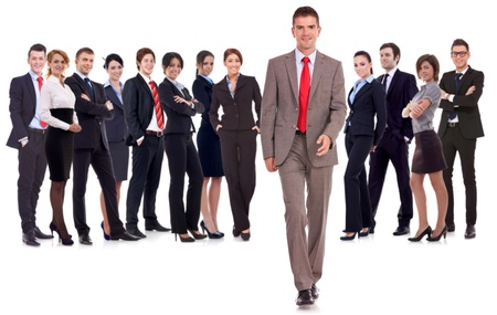 successful business team with a business man walking forward leading it - be different concept - isolated over a white background photo