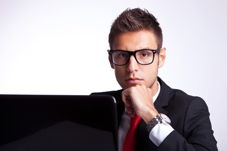 business man sitting next to laptop and thinking, looking at the camera photo