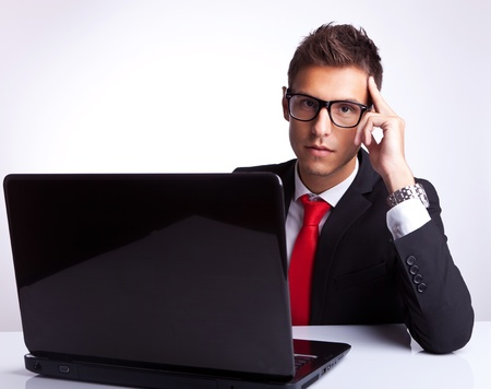 Business man sitting at office desk using laptop computer and looking at the camera, thinking photo