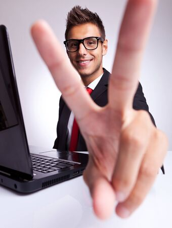 happy young man: Happy young business man showing victory gesture at office desk , smiling.