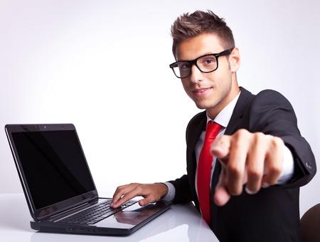 business administration: vista lateral de un hombre de negocios que se�ala su dedo hacia la c�mara mientras se trabaja en la computadora port�til