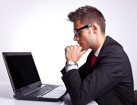 hombre de perfil: Perfil del hombre de negocios sentado en la mesa de trabajo en el ordenador port�til